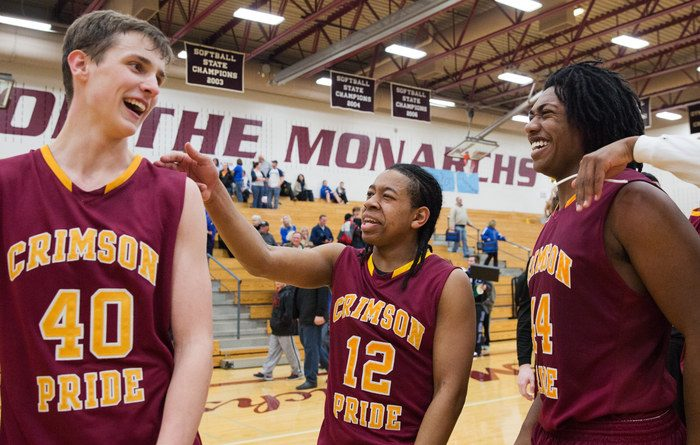 PAPILLION, NEBRASKA - 03/04/2014: Omaha Roncalli Cole Meister, No. 40, Jody Bryant, No. 12, and Derek Lee, No. 44 celebrate their victory over Bennington with a score of  56-54 in OT during the Boys Class B district B-3 final as the Bennington   Badgers take on the Omaha Roncalli Crimson Pride at Papillion-La Vista high school on Tuesday, March 4, 2014.    BRYNN ANDERSON/THE WORLD-HERALD